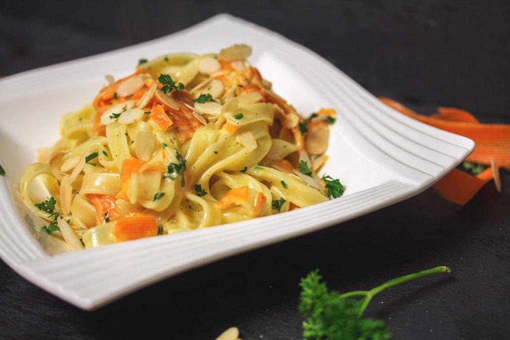 Bandnudeln mit glasierten Karotten in Sahnesoße mit Petersilie und Mandeln