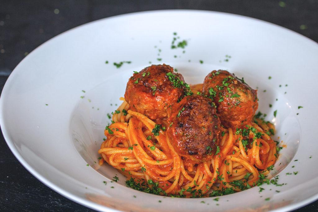 Gehacktes Bällchen mit Parmesan-Kruste in Tomatensoße auf Spaghetti