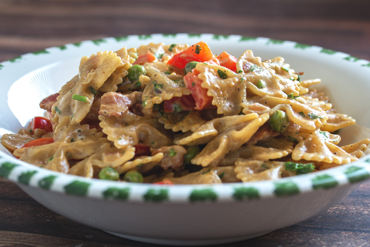 Rezept: Farfalle mit Bacon, Paprika, Erbsen & Frischkäse