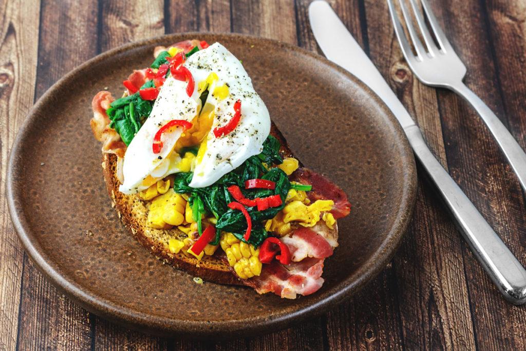 Pochiertes Ei auf Spinat, gebratenem Mais vom Kolben, knusprigen Bacon und gerösteten Körnerbrot