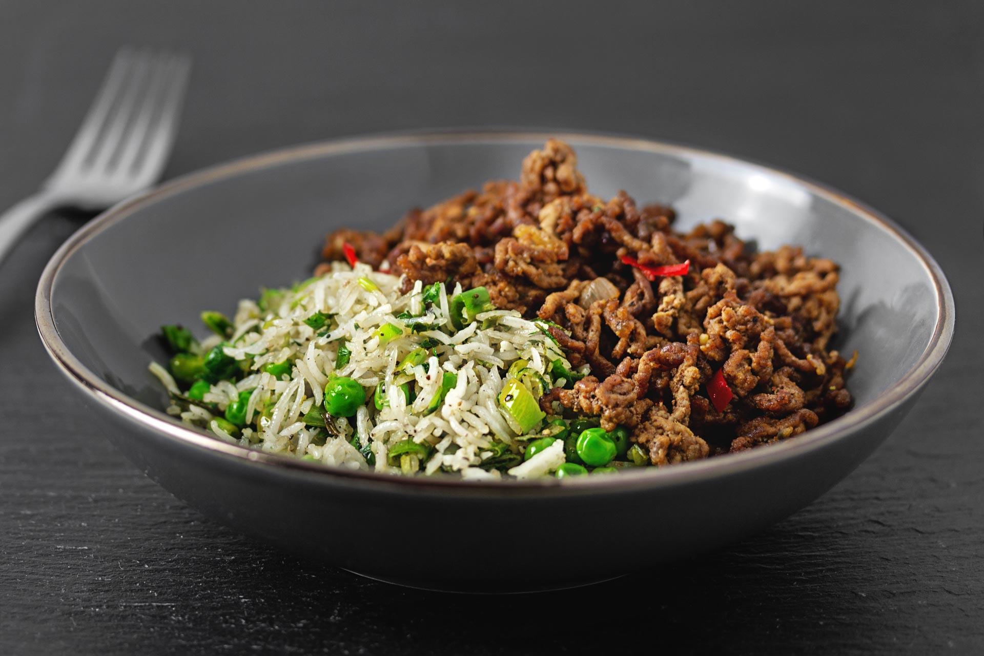Knuspriges Hackfleisch auf gebratenen Reis mit Erbsen, Frühlingszwiebeln und Petersilie